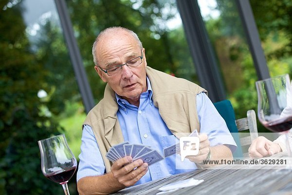 Seniorenpaar spielt Karten und trinkt Rotwein