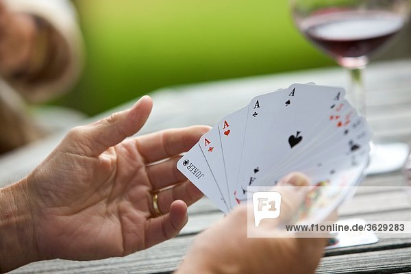 Senior spielt Karten und trinkt Rotwein  close-up