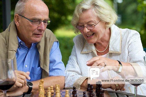 Seniorenpaar auf der Terrasse spielt Schach