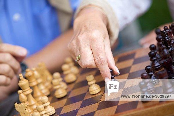 Seniorenpaar spielt Schach  close-up
