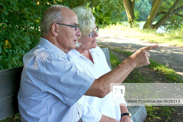 Seniorenpaar unterhält sich auf einer Parkbank