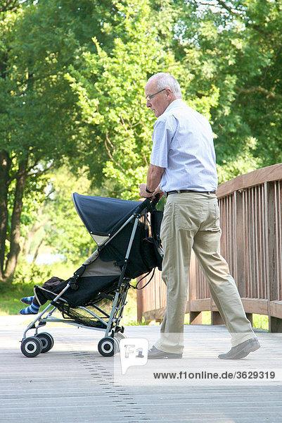 Großvater geht mit Enkelsohn im Kinderwagen spazieren