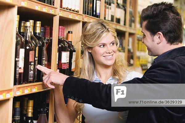 Junges paar Wein in ein Spirituosengeschäft auswählen