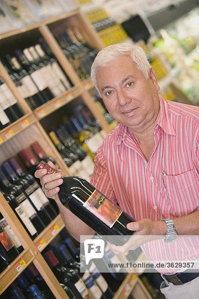 Porträt von ein älterer Mann hält eine Flasche Wein