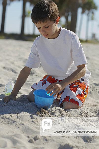 Junge hocken und spielen mit Sand am Strand