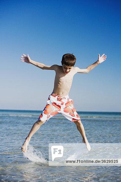 Boy springen in Wasser mit seinen ausgestreckten Armen