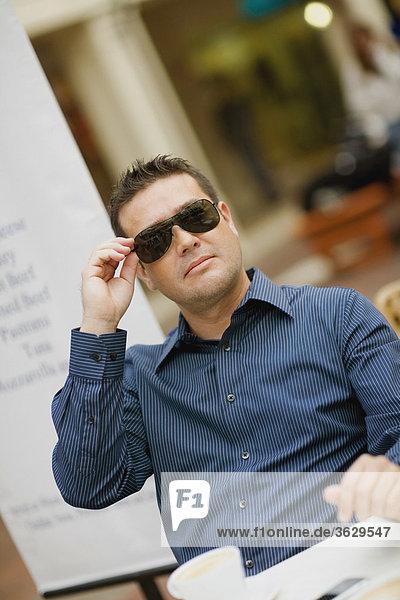 Nahaufnahme eines Mitte erwachsenen Menschen halten seine Sonnenbrille