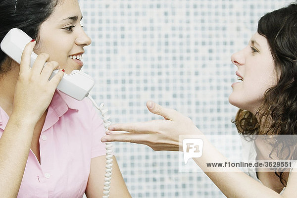 Close-up of a young woman using a telephone with her friend sitting in front of her