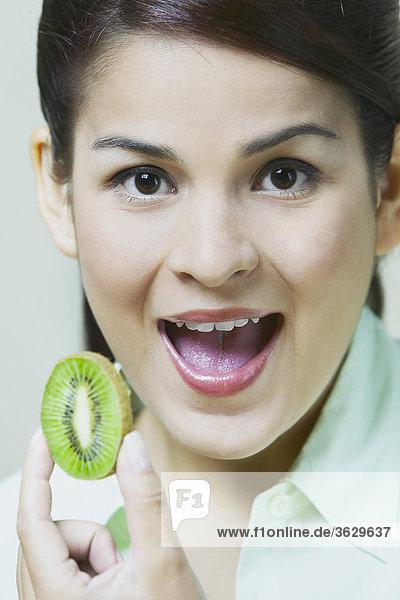 Nahaufnahme of a junge Frau hält eine Scheibe des Kiwi Obst