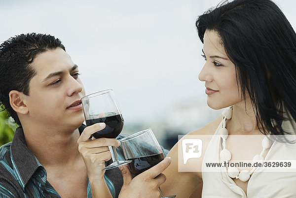 Close-up of a young couple holding glasses of wine