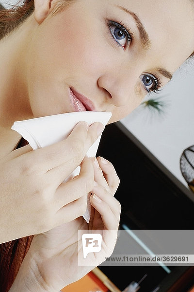 Close-up of a young woman rubbing her mouth with a tissue paper