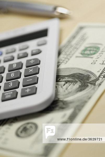 Nahaufnahme von einem Rechner und 100 Dollar Bill auf dem Tisch