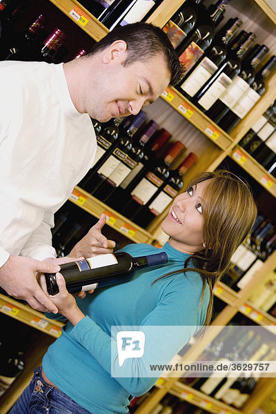 Young woman and a mid adult man in wine shop