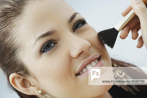 Nahaufnahme einer jungen Frau Make-up mit einem Make-up Pinsel anwenden
