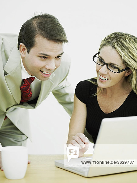 Close-up of a businessman and a businesswoman looking at a laptop