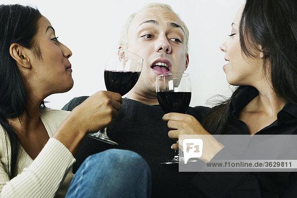 Nahaufnahme eines jungen Mannes mit zwei junge Frauen zu sitzen und halten Gläser Wein