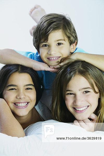 Bildnis eines Knaben mit seinen Schwestern auf dem Bett liegend