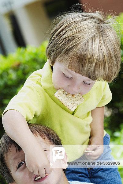 Boy Fütterung Keks zu einem anderen