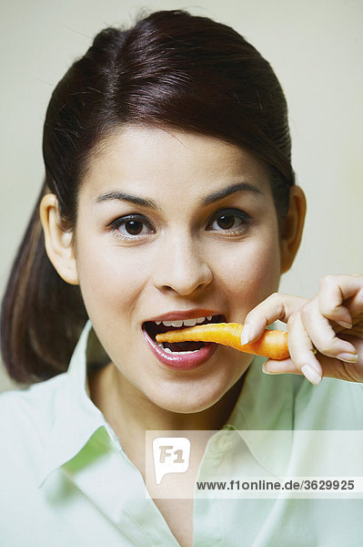 Close-up of a young woman eating a carrot