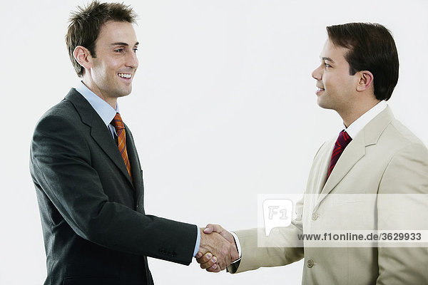Side profile of two businessmen shaking hands and smiling