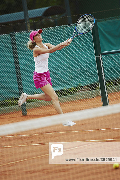 Mid adult woman playing tennis