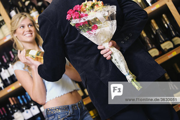 Rear view of a young man hiding bouquet of flowers behind his back from a young woman