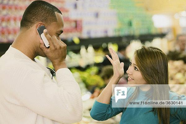 Seitenansicht eines jungen Mannes sprechen auf ein Handy und eine junge Frau auf der Suche nach ihm