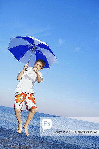 Bildnis eines Knaben mit einem Regenschirm springen