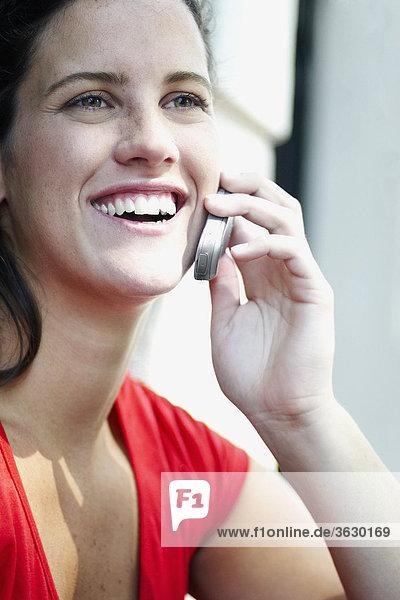 Nahaufnahme of a junge Frau hält ein Mobiltelefon und lachen