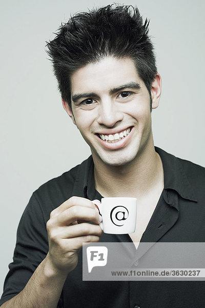 Porträt eines jungen Mannes hält eine Tasse Tee und lächelnd