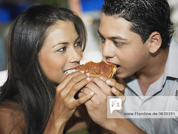 Close-up of a young couple eating a burger