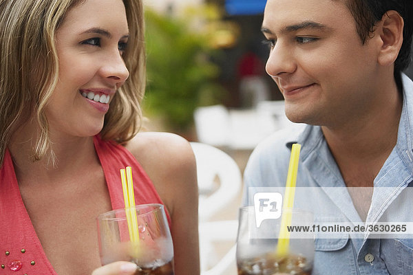 Close-up of a young couple holding glasses of cold drinks
