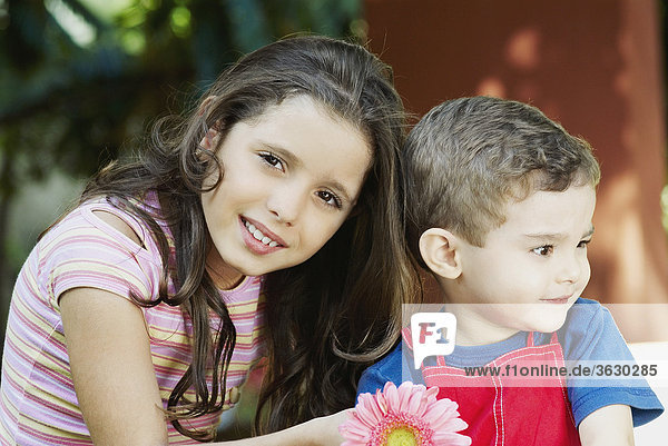 Portrait of a girl smiling with a boy beside her