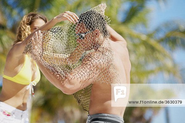 Junge Frau setzen ein Fischernetz über ein junger Mann