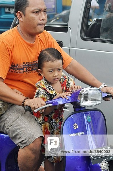 Ubud (Bali  Indonesia): a man driving a Vespa carrying a branch and his daughter