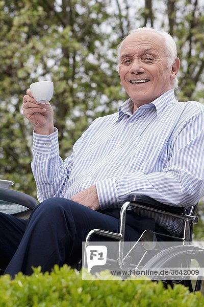 sitzend Portrait Mann trinken Tee Rollstuhl