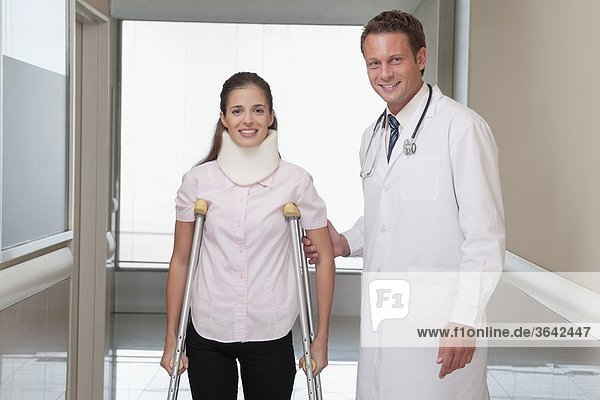 Doctor assisting a patient to walk in a hospital corridor