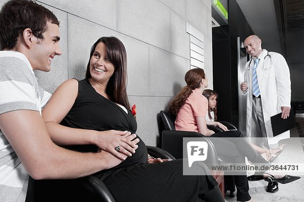 Patienten und ein Arzt in einem Warteraum