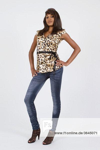 Junge Frau mit Leoparden-Oberteil  Jeans Leggings und hochhackigen Schuhen  stehend