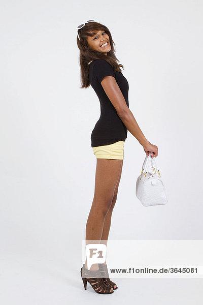 Junge Frau in Hotpants und hochhackigen Schuhen  mit weißer Handtasche  stehend