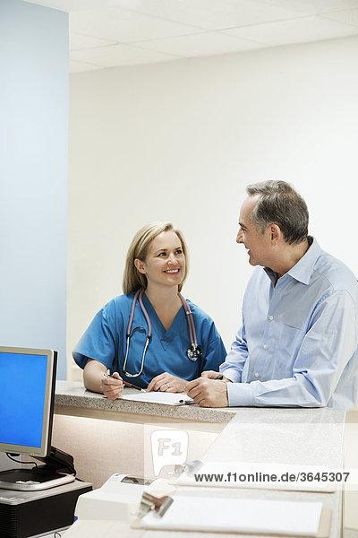 Patientin sprechen Arzt Krankenhaus grüßen Tresen
