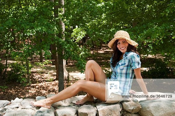 32 year old brunette woman in casual summer dress sitting on a stone wall smiling at the camera.