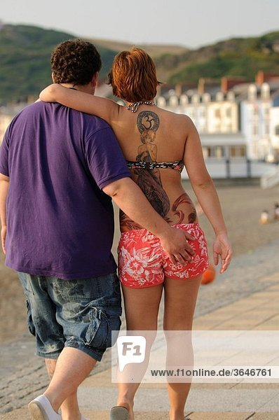 A young couple walking arm in arm  woman with tattooed back  Aberystwyth Wales UK