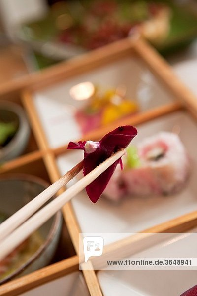A piece of sushi being held in chopsticks over a plate of sushi in a restaurant.