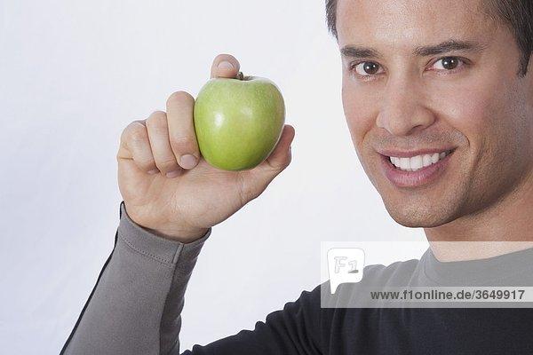 Mann  hält einen grünen Apfel