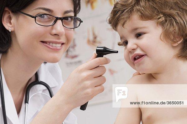 Arzt untersucht einen Baby-jungen mit einer Otoskop