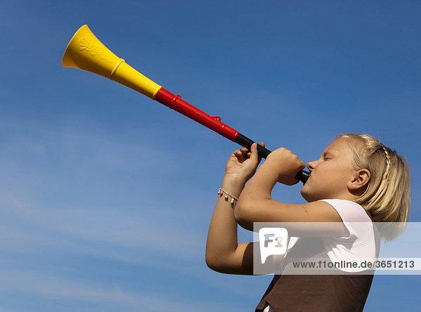 Mädchen,  8 Jahre,  mit einer Trompete in den Farben schwarz rot gold,  Deutschland