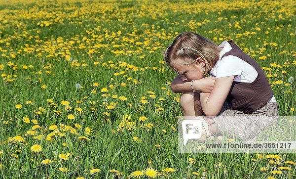 8-jähriges Mädchen sitzt auf Wiese,  beobachtet die Natur