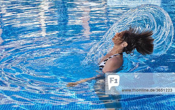 Frau im Swimmingpool erzeugt eine Wasserfontäne