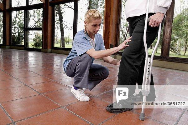 Frau gehen Hilfe Physiotherapie